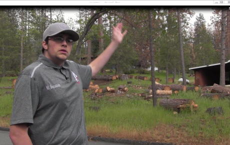 Michael Beaudoin from the Mariposa County Fire Safe Council in front of a home surrounded by dead trees.