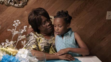Image from HBO documentary FOSTER featuring adult woman holding young girl.